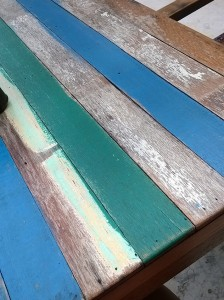 Distressed painted wood table tops at the beach resort.